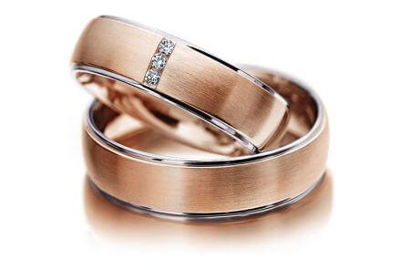 Rosegoldene Ringschiene mit drei eingefassten Diamanten.
