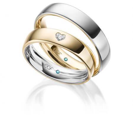 eduard g fiedel - klassische Trauringe. Der Herrenring besteht aus Weißgold aussen und innen aus Gold. Der Damenring hat als Highlight einen gefassten Herzförmigen Diamanten.